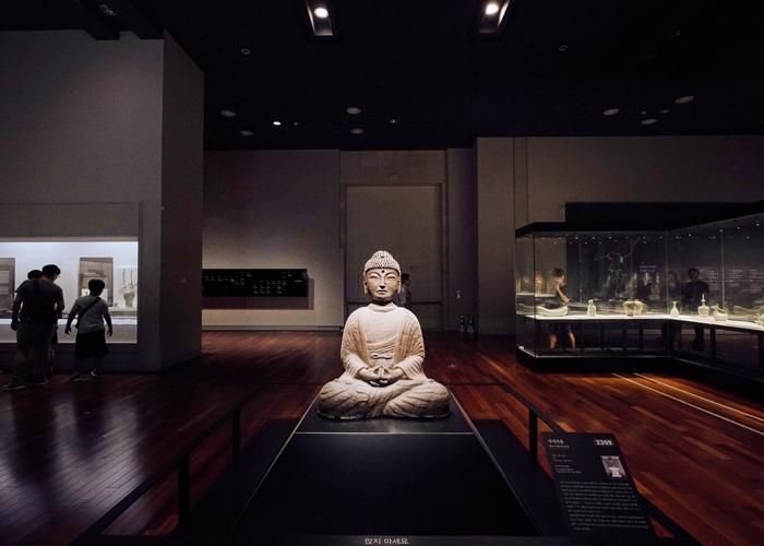 Буддийская статуя внутри музея, сзади которой виднеются другие экспонаты и люди, гуляющие по музею