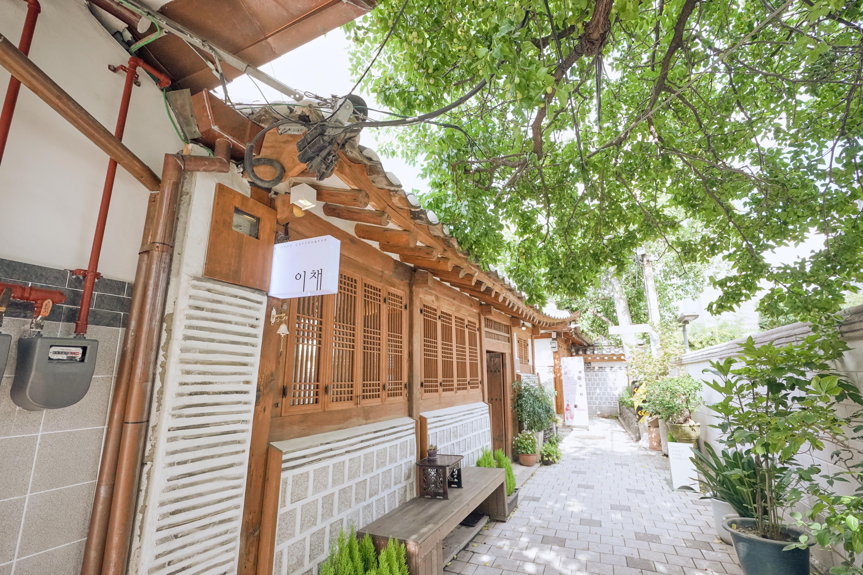 Фотография ханока сверху которого весит белая вывеска с названием кафе. Справа виднеются зеленые деревья.