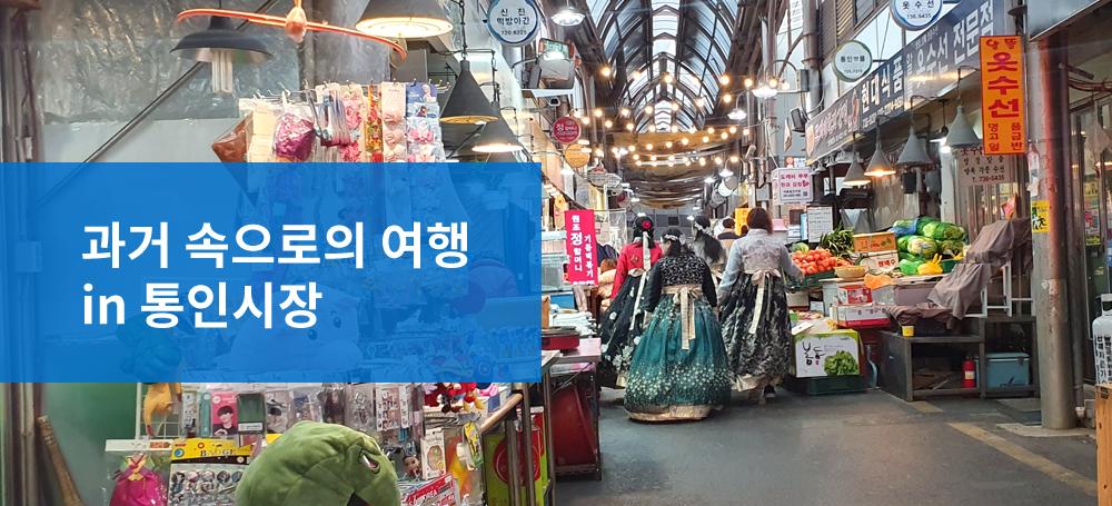 과거 속으로의 여행 in 통인시장 이라고 적힌 파란색 박스와 뒤로 보이는 통인시장의 양옆으로 놓여진 야채 상점들과 한복을 입고 걸어가는 세명의 사람들