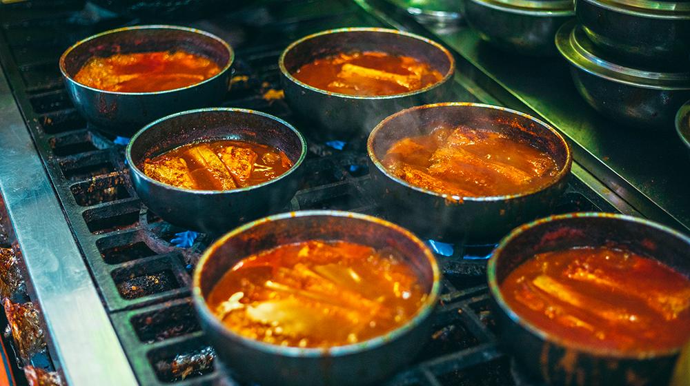 Six bowls of galchi-jorim cooking on a restaurant stovetop