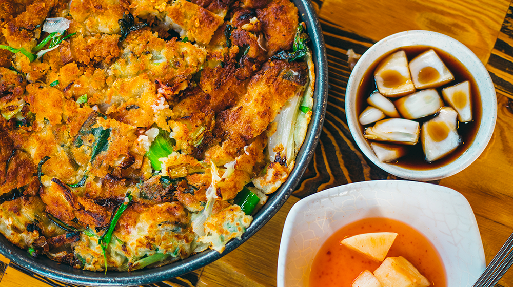 A hearty, thick served of pajeon next to a small bowl of soy sauce and radish kimchi