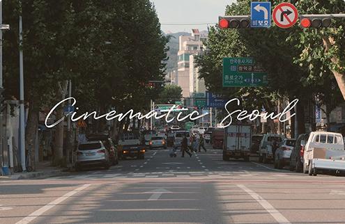 Фотография автомобильной дороги с зелеными деревьями с двух сторон, с надписью Cinematic Seoul посередине
