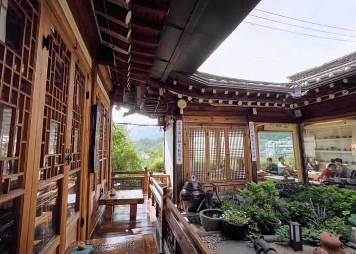 客人坐在有韩屋地台的韩屋咖啡厅中。