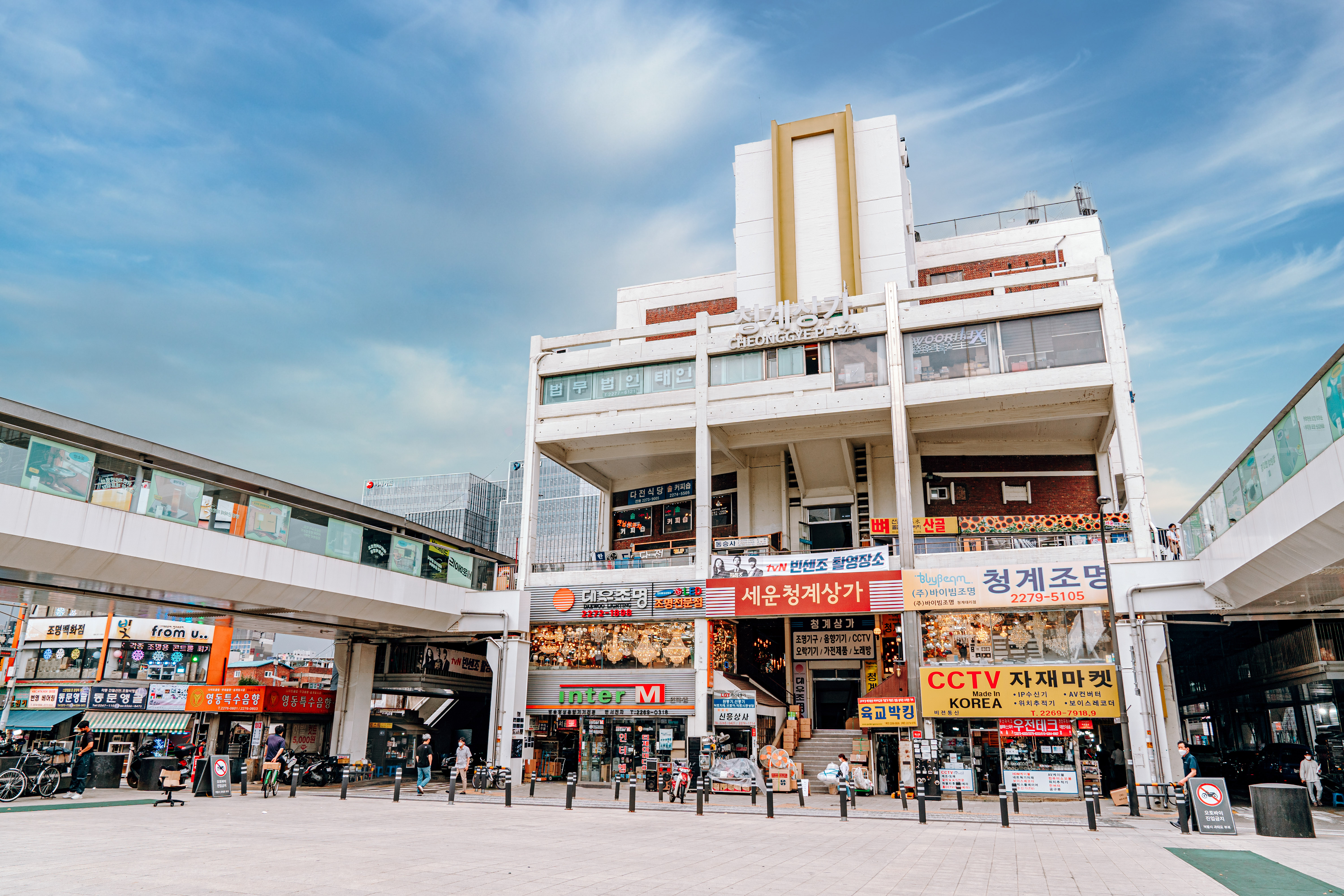 A photo of Sewoon Shopping Center. There are various signs and posters hanging on the front of the building. There are people outside the front entrance as well.