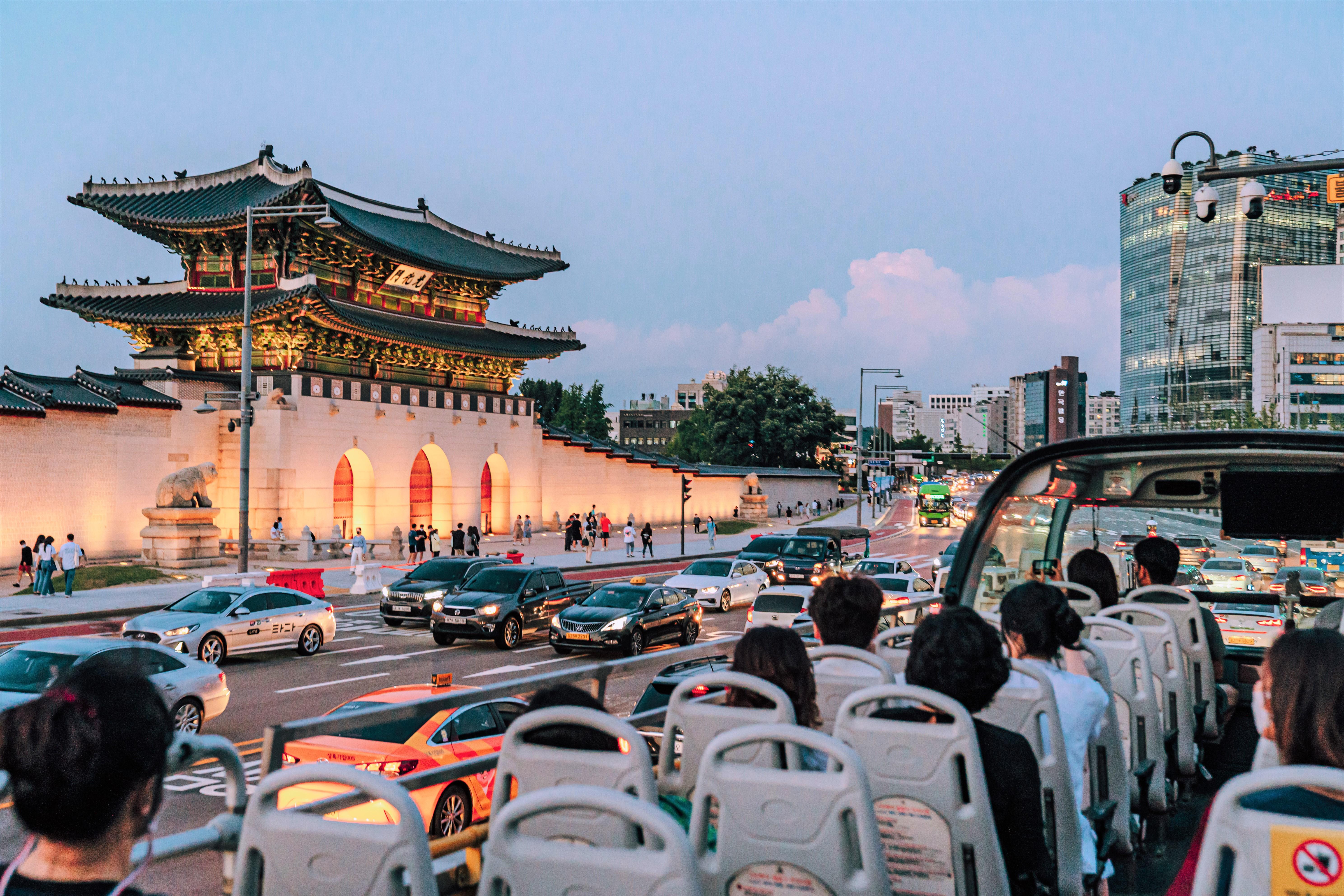 首爾市內的車道經過的首爾城市觀光巴士,乘坐首爾城市觀光巴士的人、道路上的車子還有燈亮着的光化門