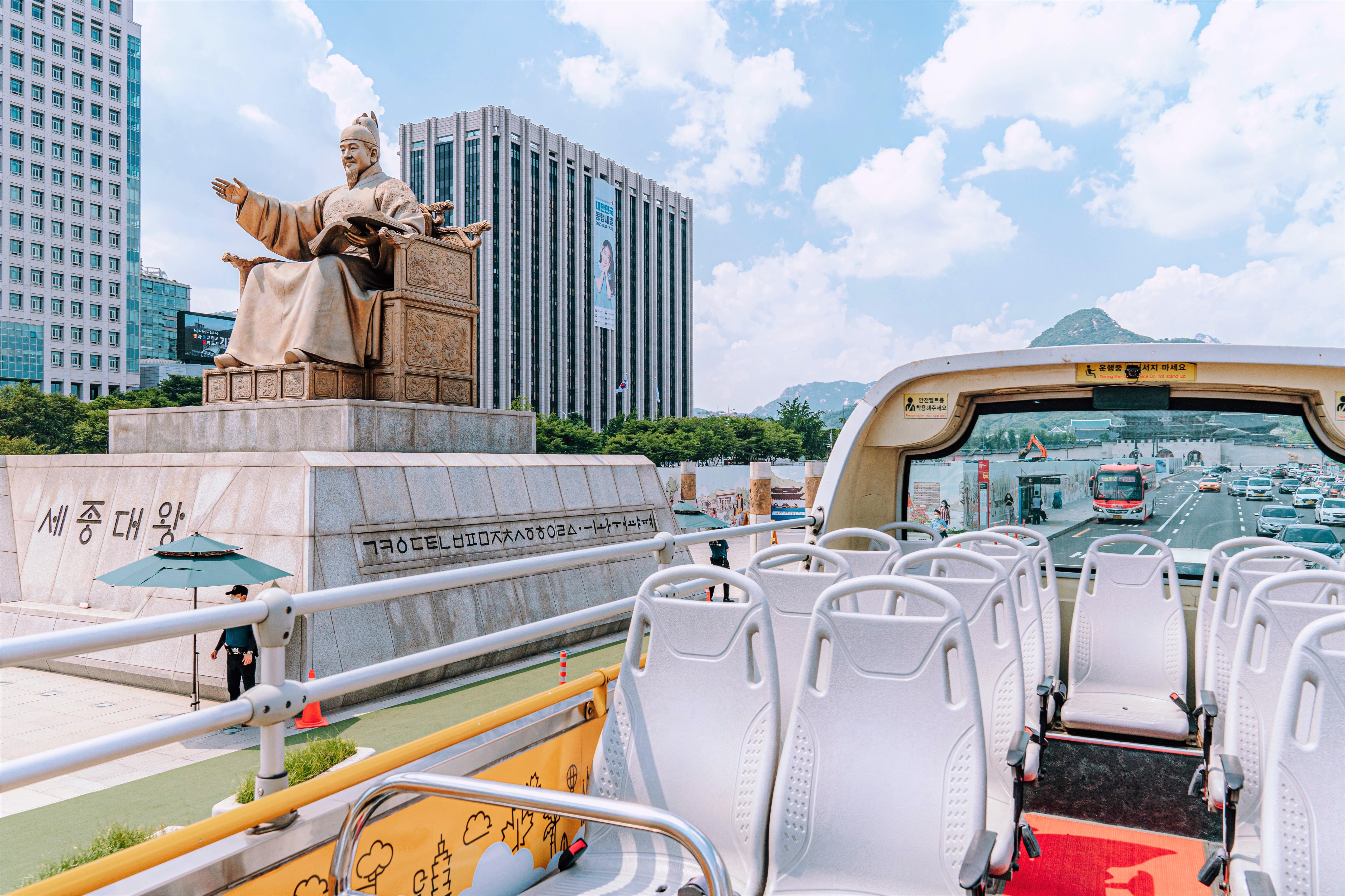 在首爾城市觀光巴士上看到的世宗大王銅像和後面美麗的雲彩、天空和道路上的車輛