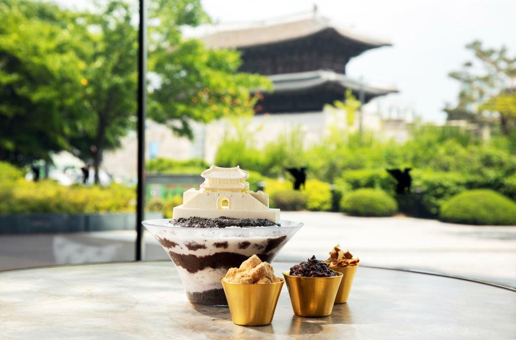 Gambaran Bingsu yang dihiasi dengan coklat yang berbentuk Heunginjimun beserta 3 mangkuk kecil yang berisi isi tambahan. Terlihat juga gerbang Heunginjimun di latar.
