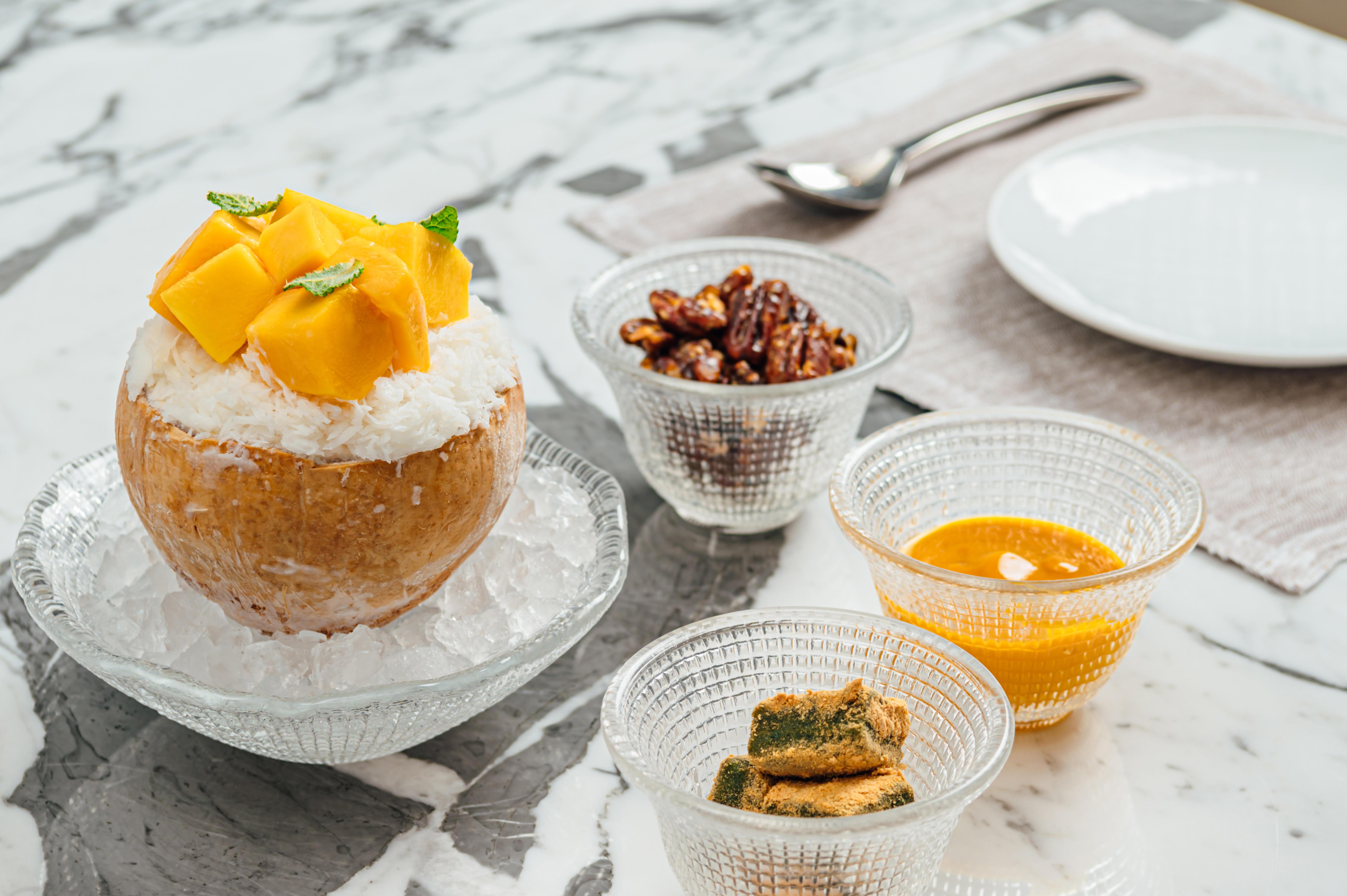 Bingsu Kelapa Mangga yang disajikan didalam tempurung kelapa, terdapat 3 mangkuk kecil yang mempunyai isi tambahan.