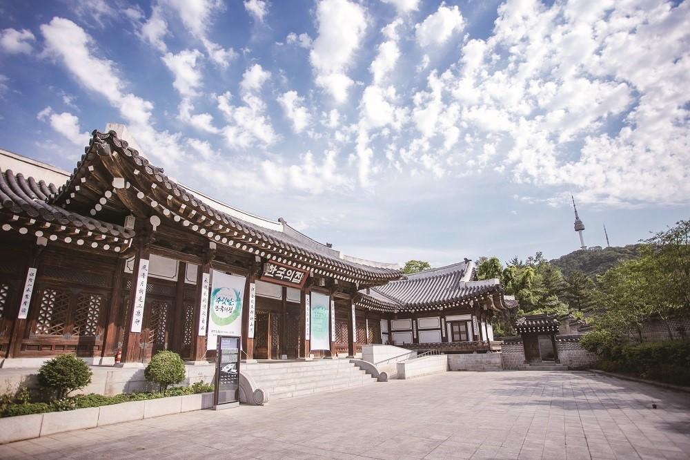 한옥 외관의 한국의집 전경이 서울의 푸른 하늘을 배경으로 보인다.