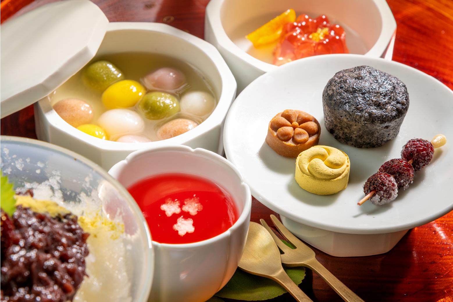 Корейские традиционные сладости вблизи. На белой посуде видно разноцветные рисовые пирожки и красный чай из плодов лимонника