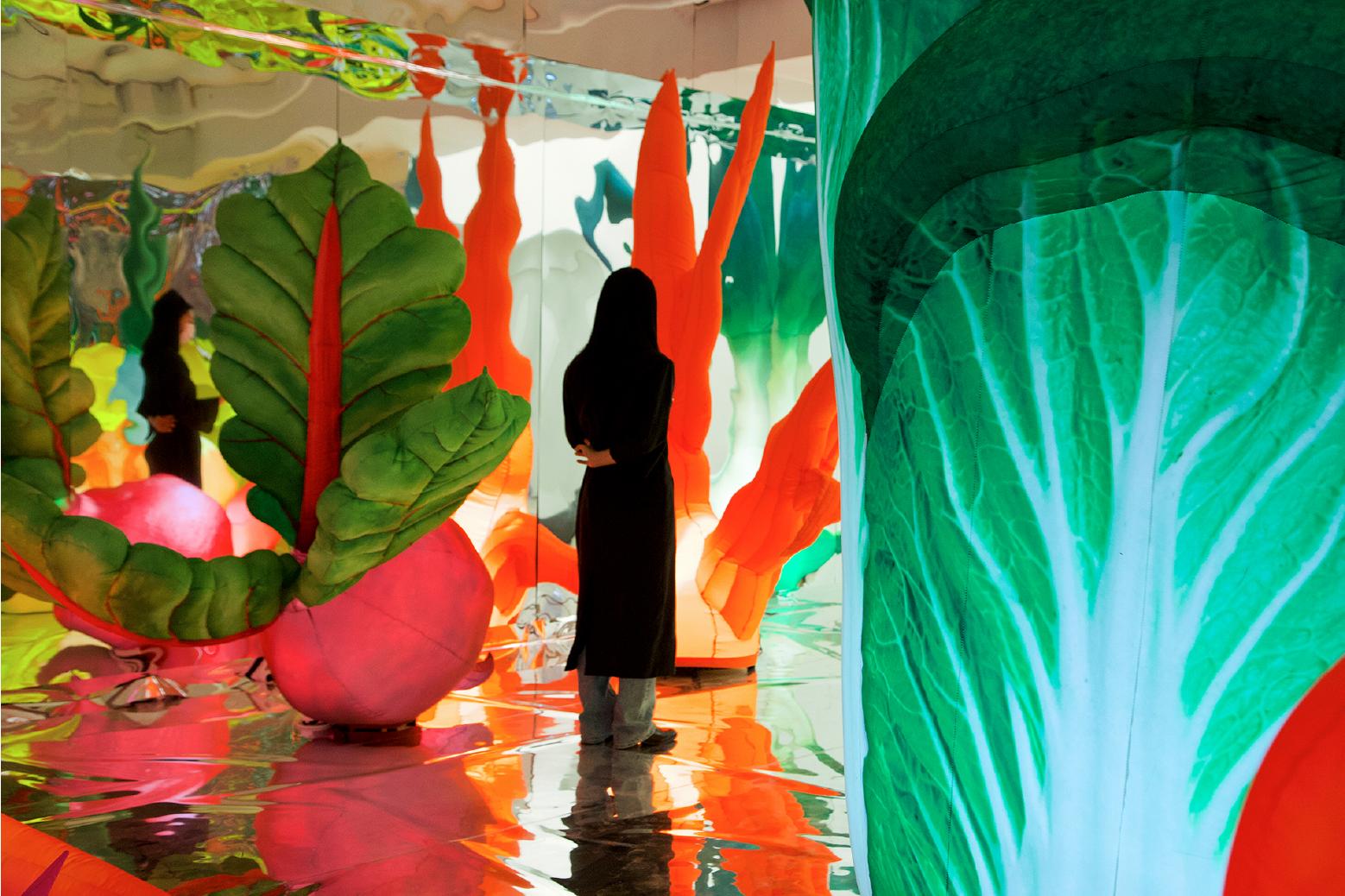 Девушка стоит между большими разноцветными инсталляциями, похожих на овощи.