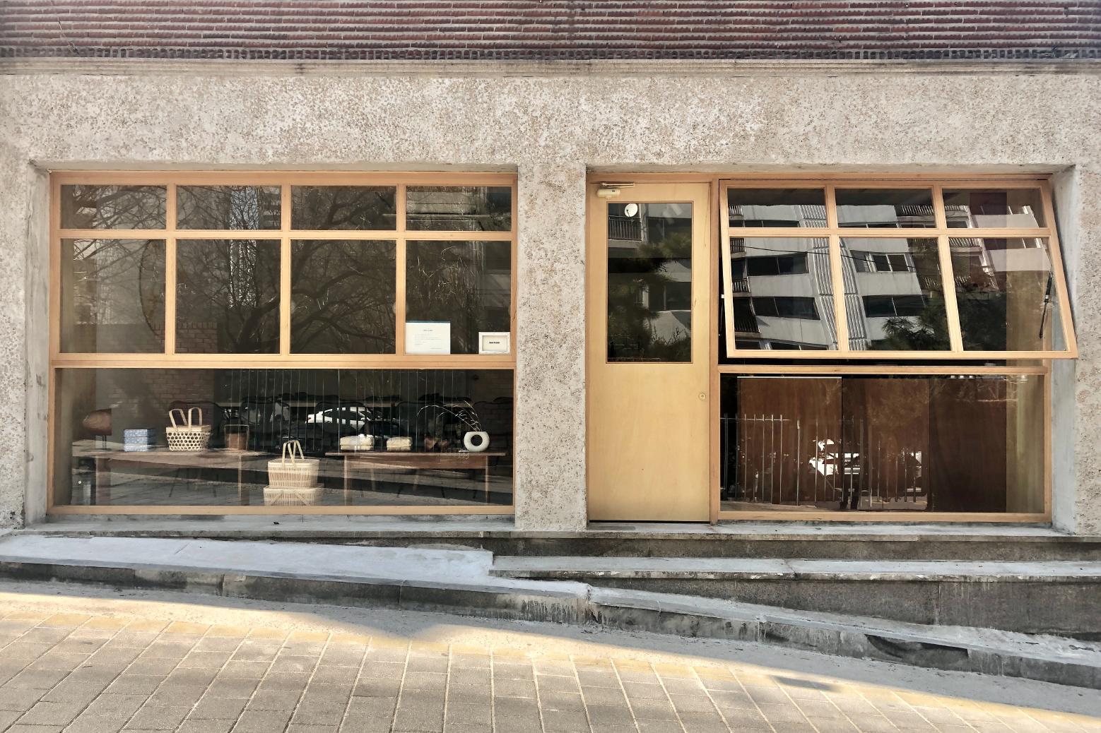 Вид на здание ресторана с большими приоткрытыми окнами, по одному слева и справа.