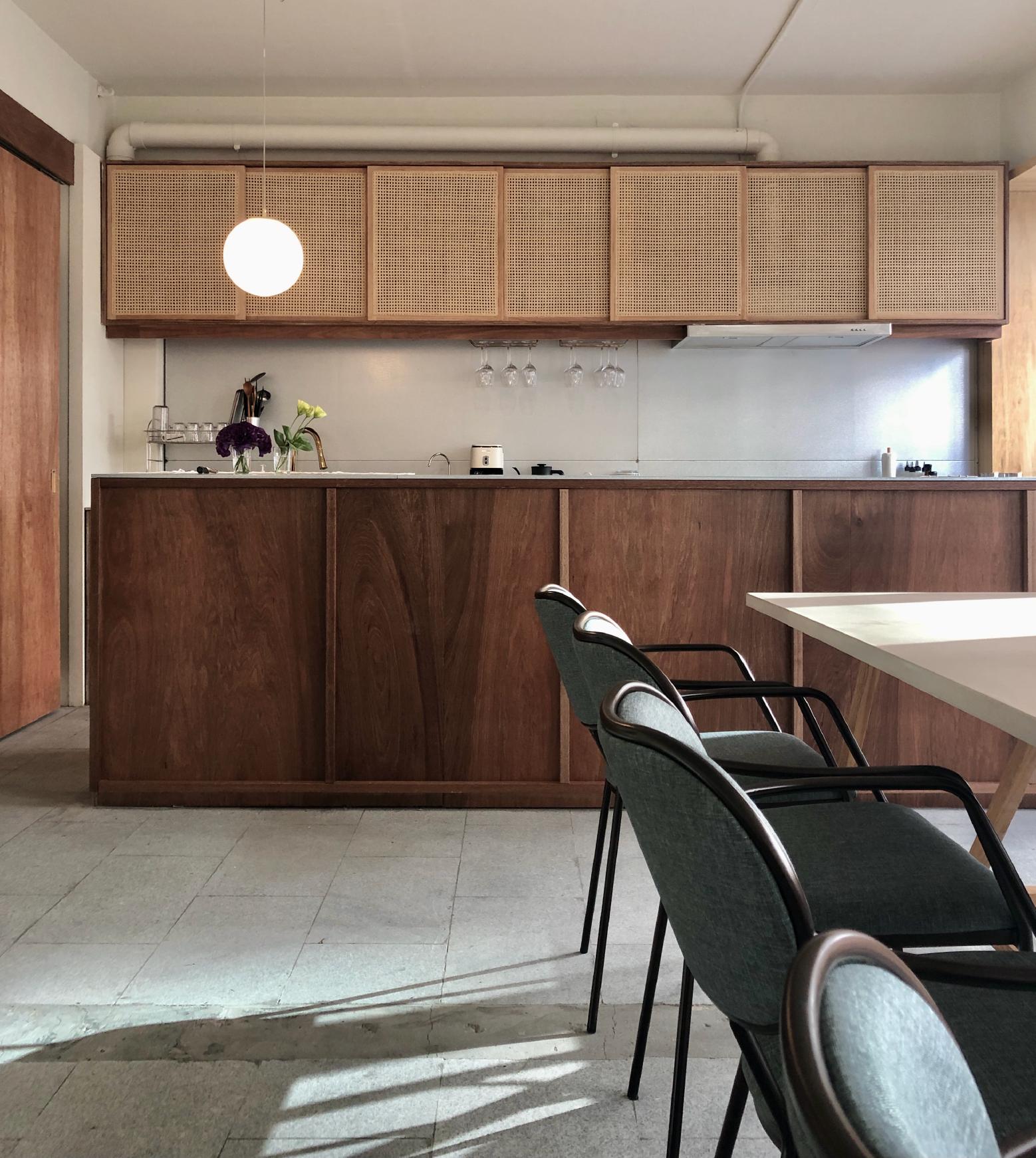 Три стула и белый стол, а на заднем плане - кухня открытого типа с деревянной мебелью.