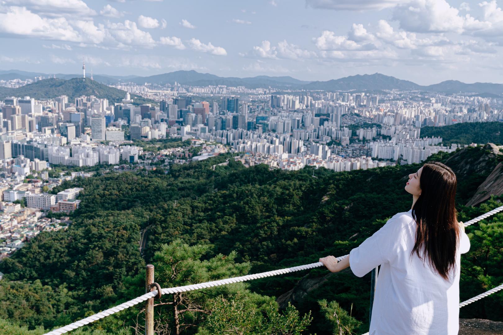 흰색 옷을 입은 여자가 산에서 서울 전망을 보고 있다.