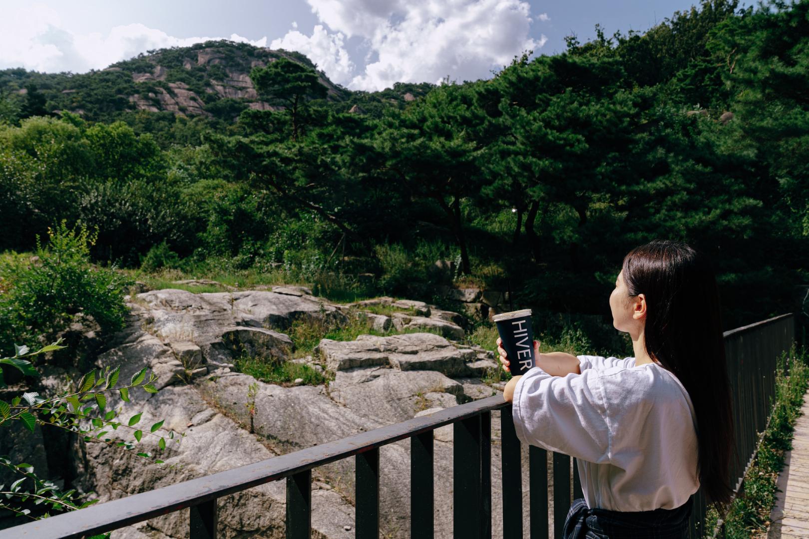 커피를 들고 있는 여자가 난간에 몸을 기대어 계곡 풍경을 구경하고 있다.