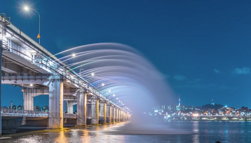 A fountain is pouring water in a curved line from the illuminated Banpyo Bridge.