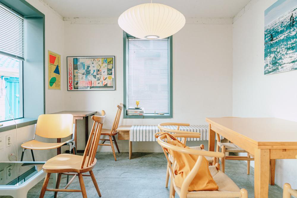 Интерьер кофейни Dewey Coffee с деревянными столами и стульями, белыми стенами, на которых висят картины