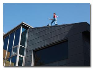 지붕 위를 걷는 여자 조형물이 있는 건물